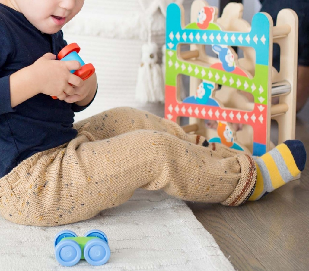 baby playing with wooden car with ramp car tower in background