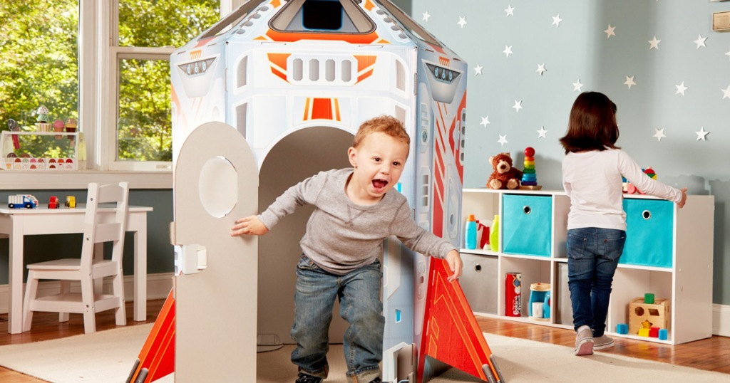 boy running out of rocket ship shaped playhouse inside of playroom