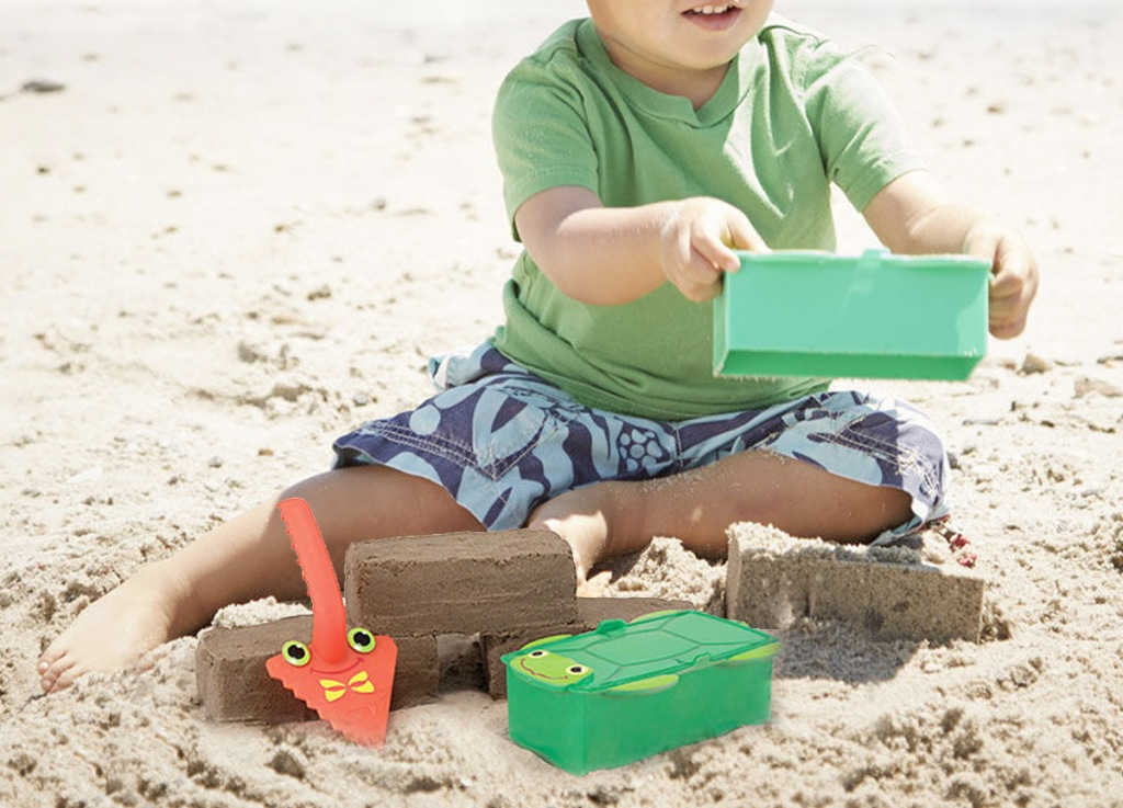 boy playing in sand on beach with green sand toy and orange shovel