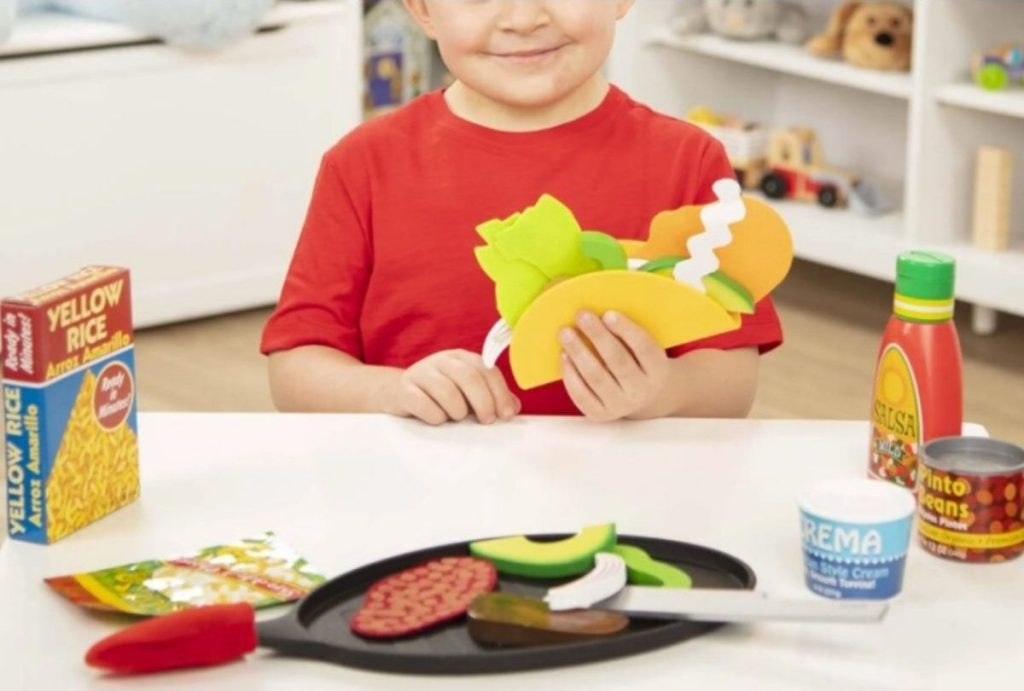little boy playing with a taco play set