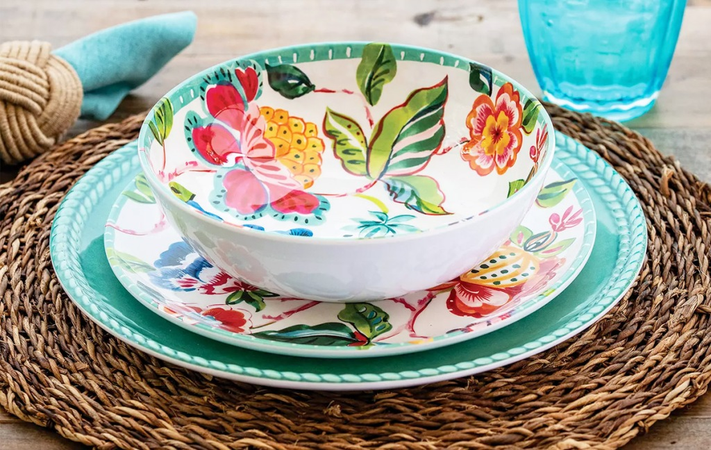 set of floral print bowl and salad plate on top of a solid color turquoise dinner plate on a wicker place mat