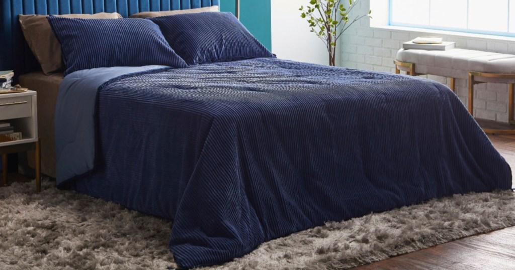bedroom with dark blue comforter on bed