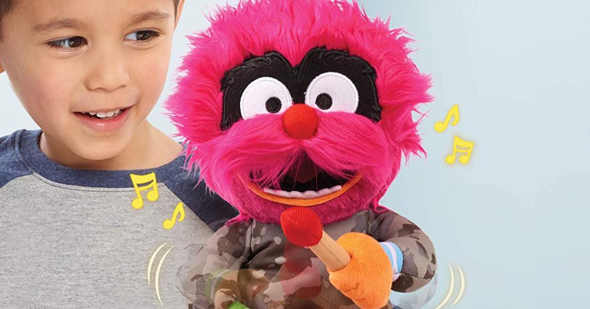 child playing with singing animated Muppet plush