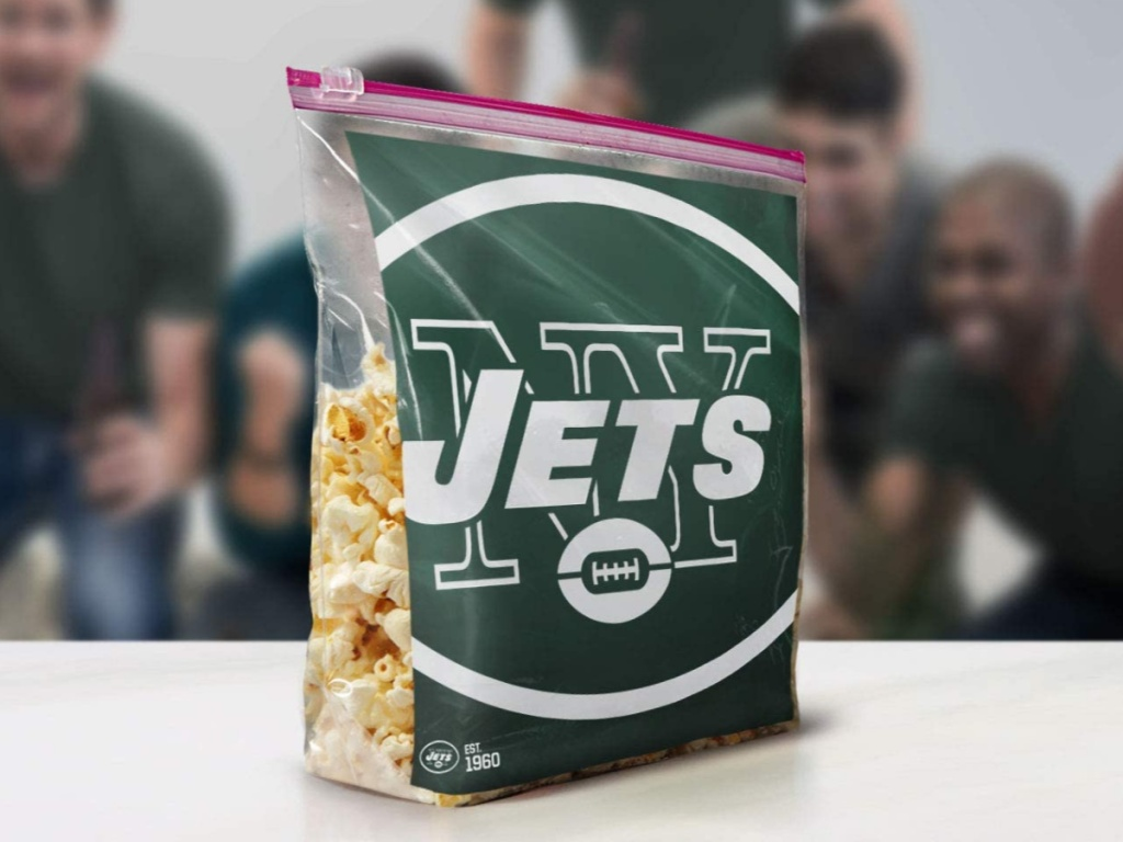 NFL team storage bag filled with popcorn on table with people gathered in background