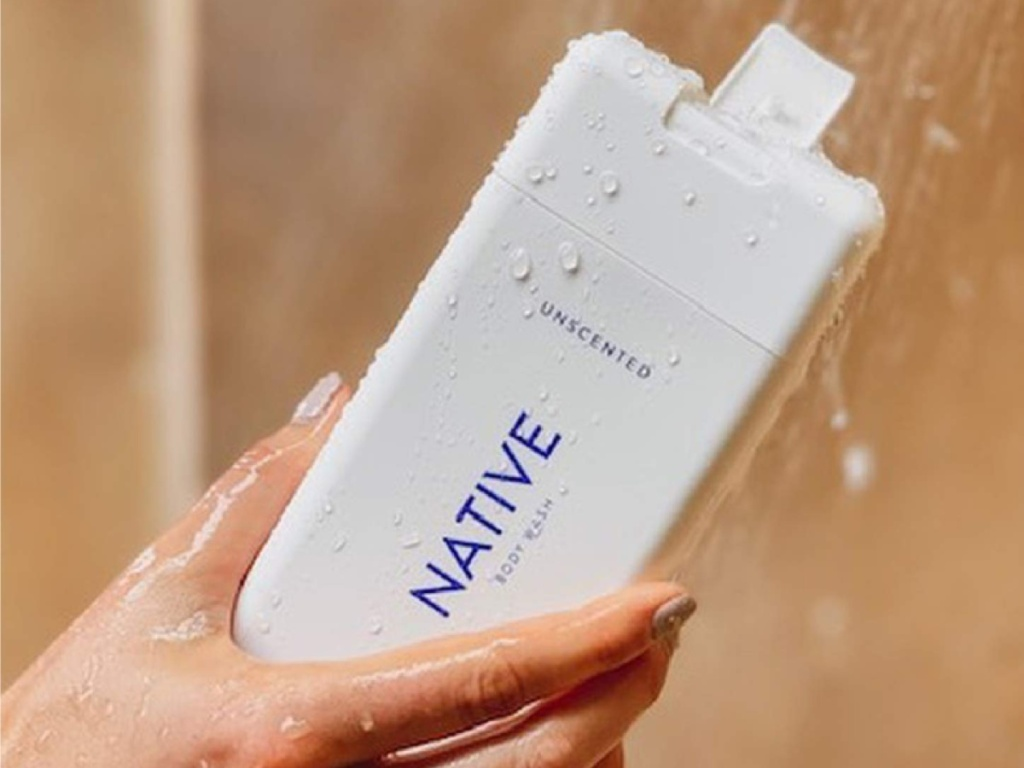 hand holding native body wash in a shower