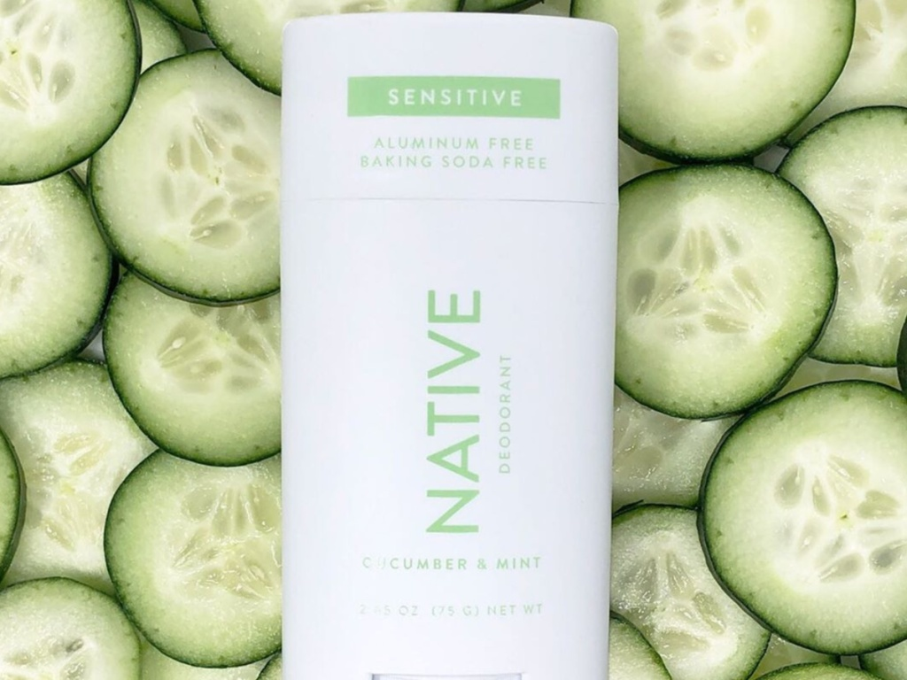 Native cucumber and mint natural deodorant laying on top of fresh cucumbers