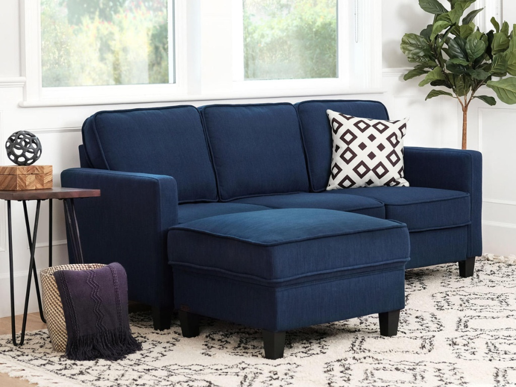 Navy Blue Sofa and Ottoman Set in a small room next to a table
