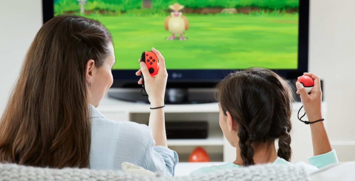 woman and girl sitting on couch playing game with Nintendo Switch gaming console and Poke Ball controllers on TV