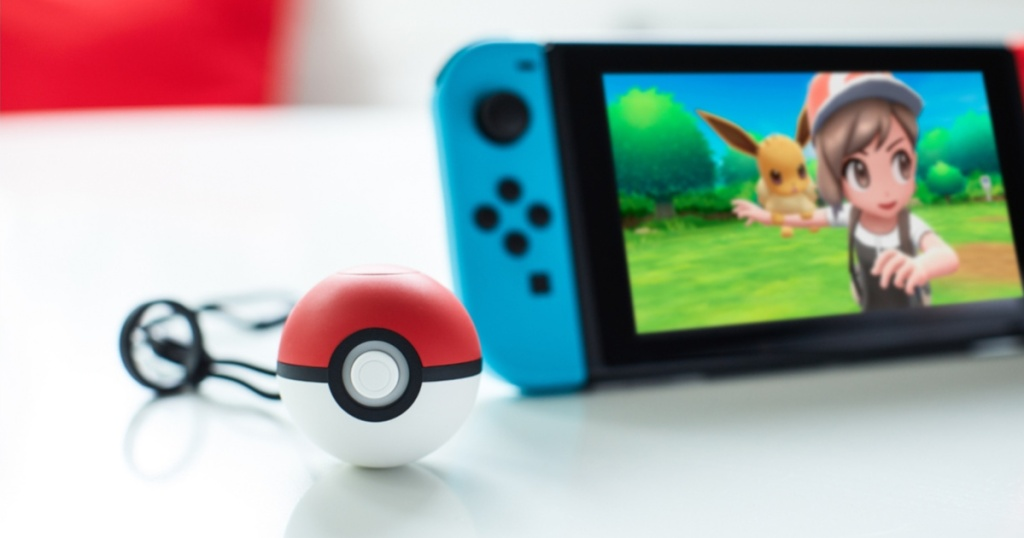 Nintendo Switch gaming console and Poke Ball controller on table
