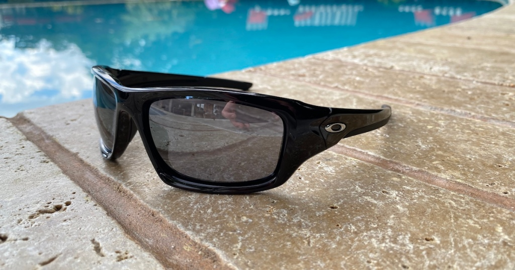 pair of Oakley Men's Valve Sunglasses sitting on pool side deck area