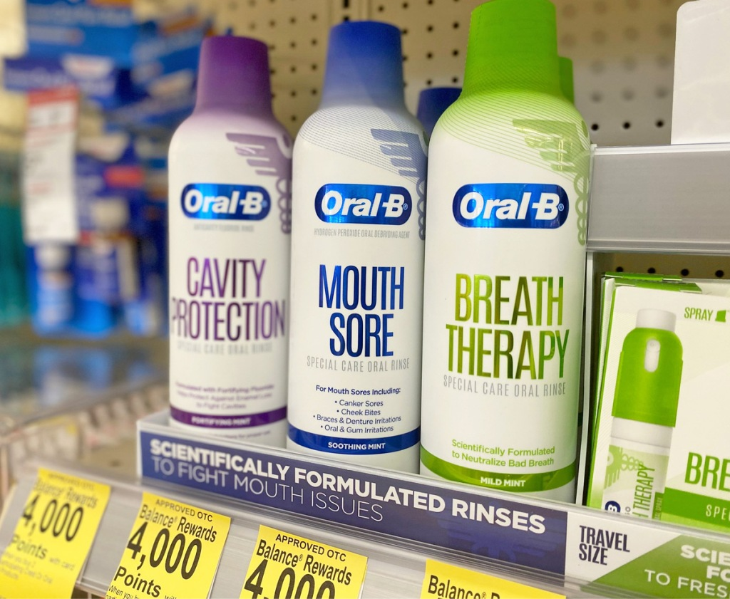 thee cans of oral-b specialty mouth washes on a store shelf