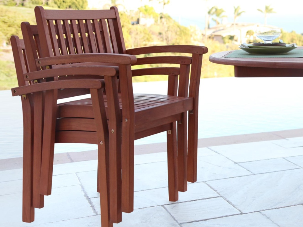 multiple outdoor patio chairs stacked together next to a table