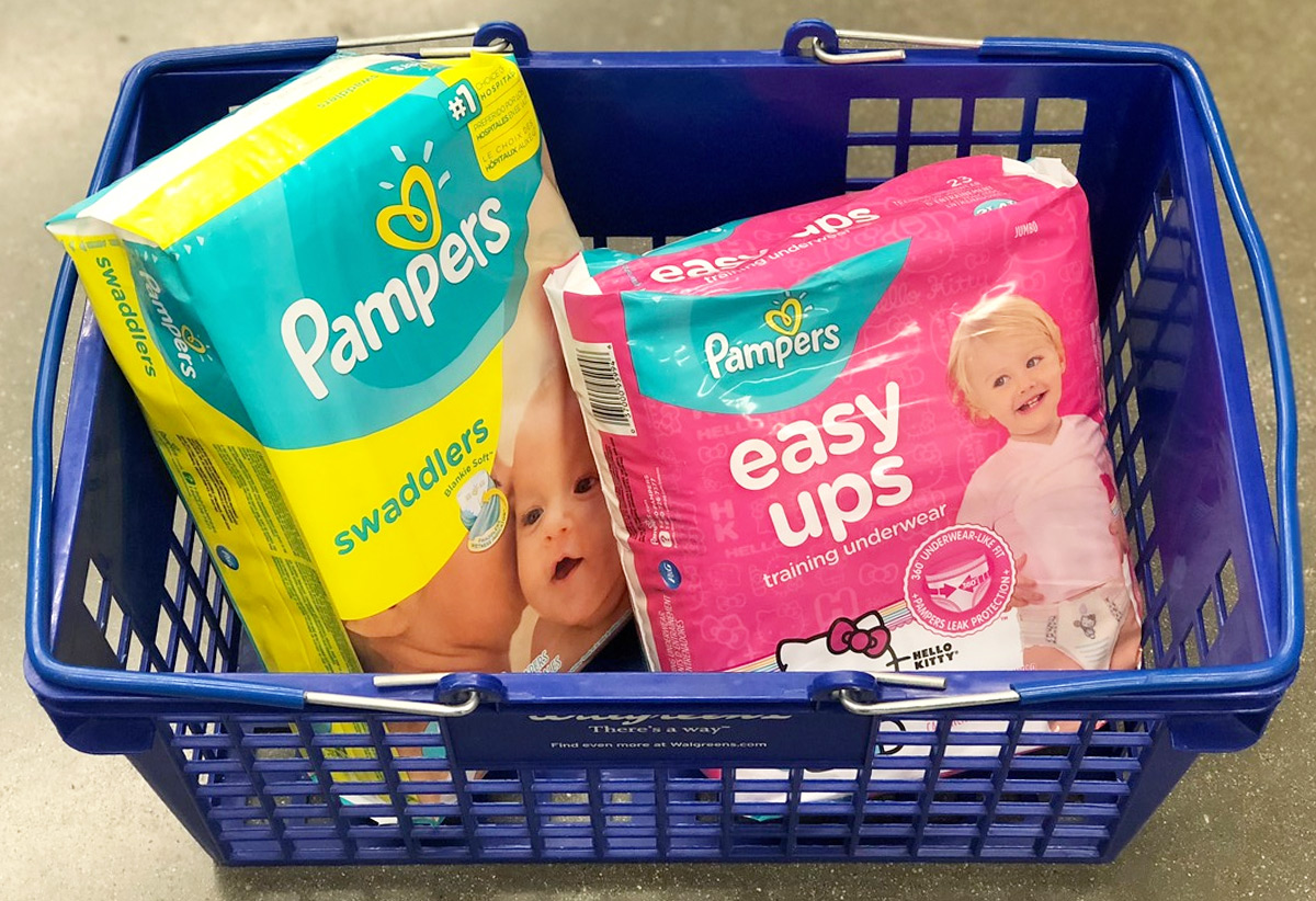 yellow and teal colored package of pampers diapers and pink package of easy-ups in blue shopping basket