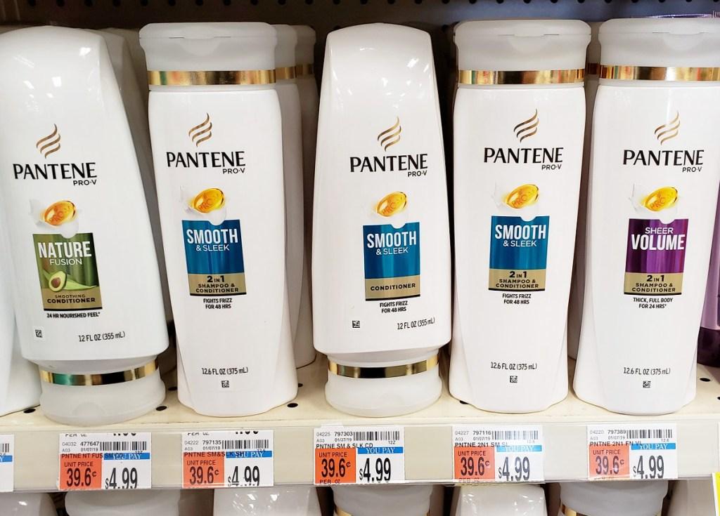 white bottles of pantene brand shampoo and conditioner on store shelf