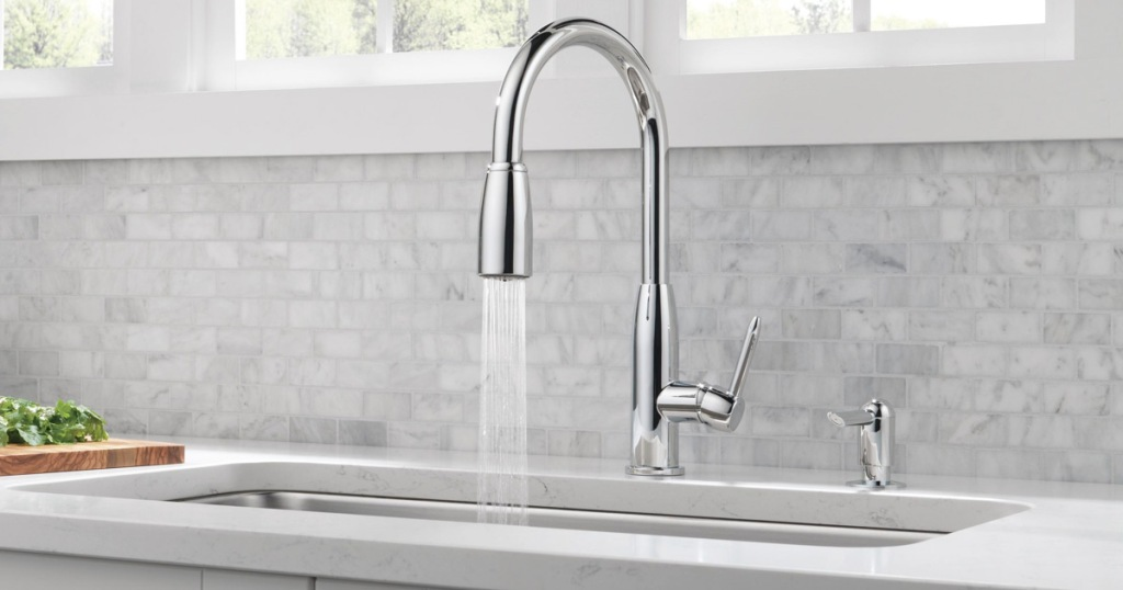 chrome kitchen faucet with running water and matching soap dispenser