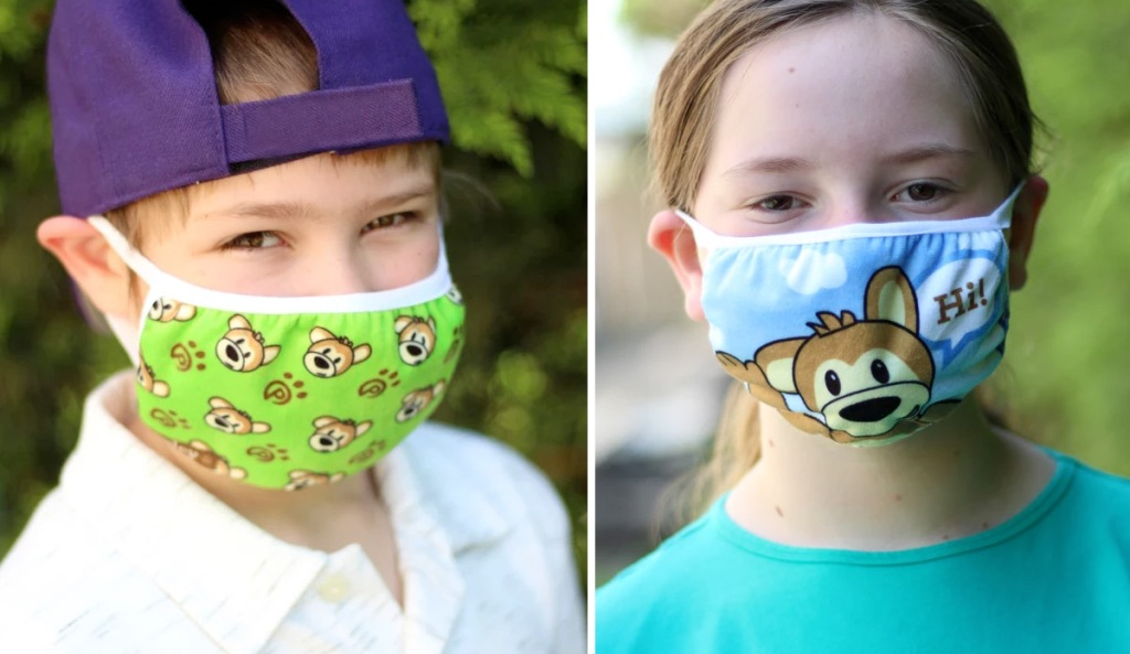 boy wearing green bear print face mask and girl wearing blue face mask with teddy bear saying hi printed on it