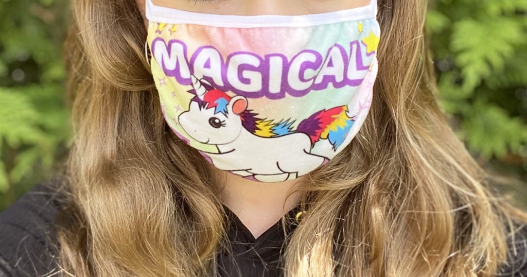 woman with blonde hair wearing a reusable cotton face mask with a unicorn printed on it