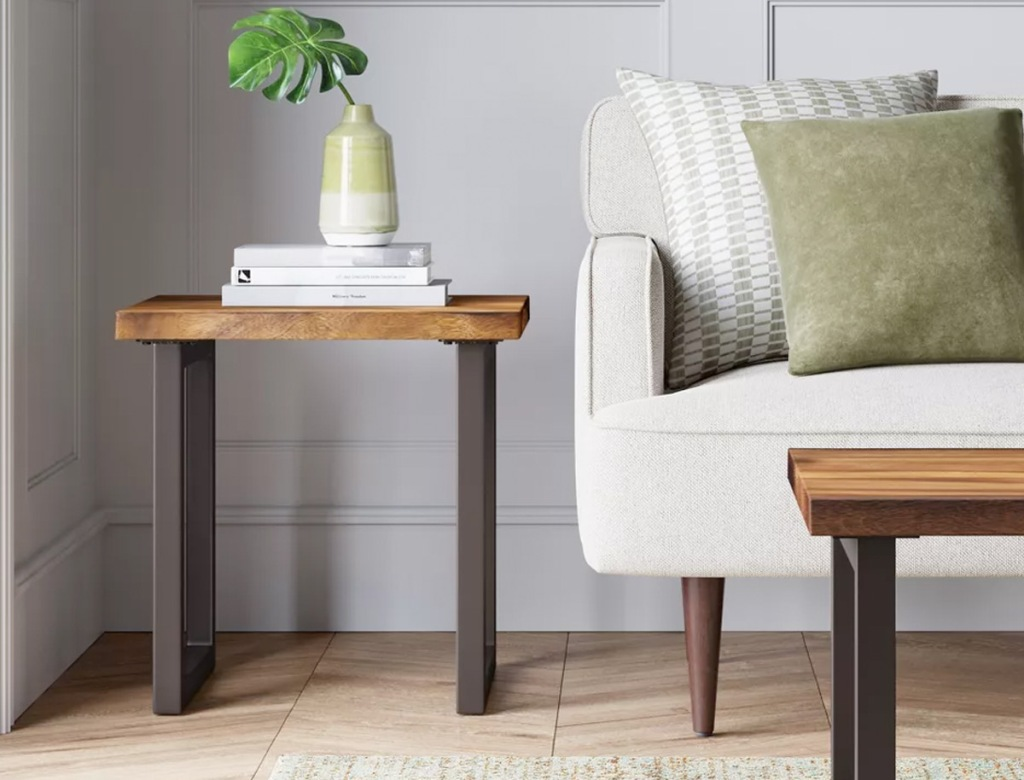 brown side table with metal legs and wood top next to a white couch