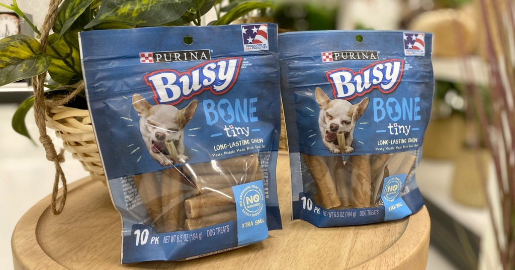 two blue bags of purina busy bone dog treats on wooden table