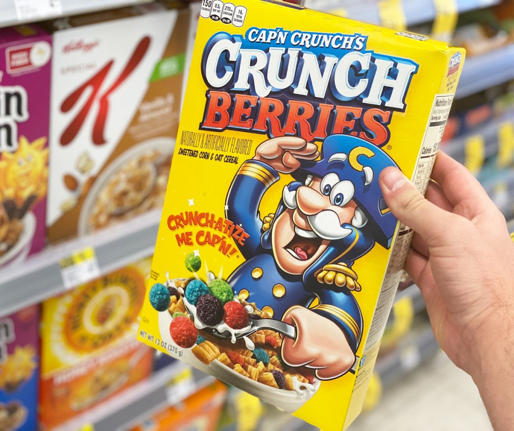 person holding a yellow box of capn crunch berries cereal in front on shelves of cereal