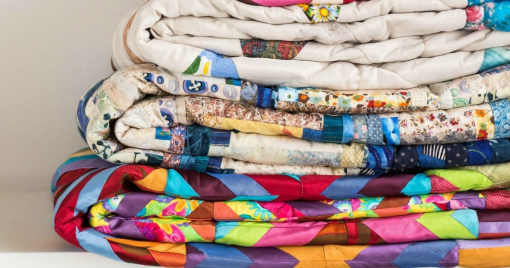 various quilts folded perfectly and stacked on top of each other