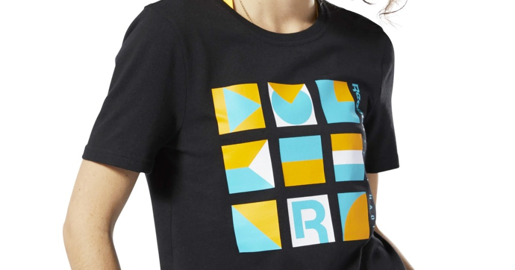 woman wearing a black graphic tee with yellow, white, and blue abstract design