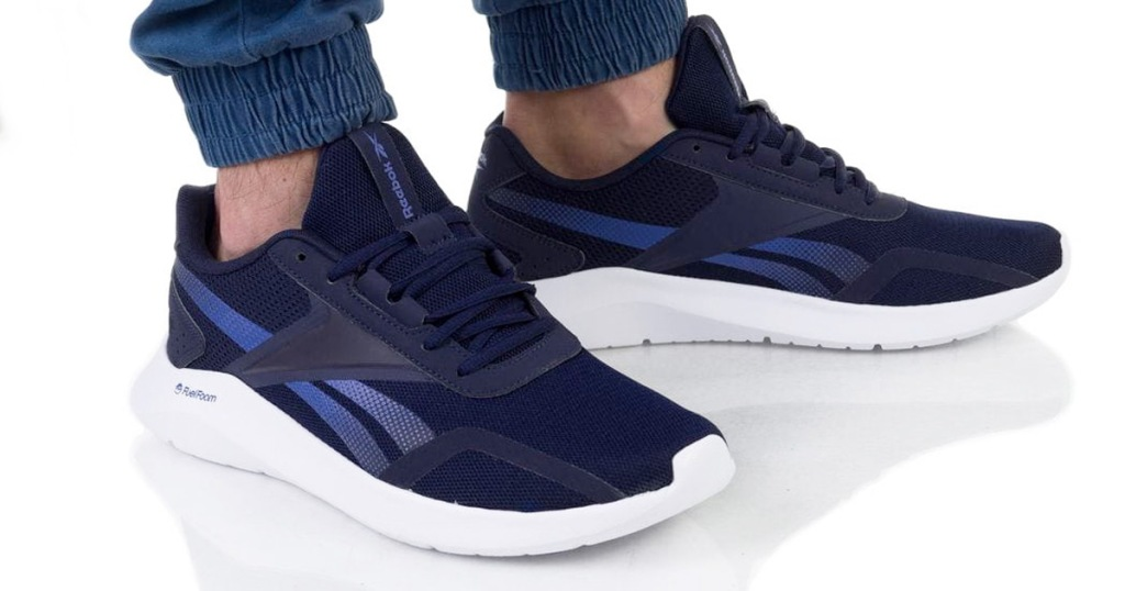 person wearing a pair of blue running shoes with white foam soles
