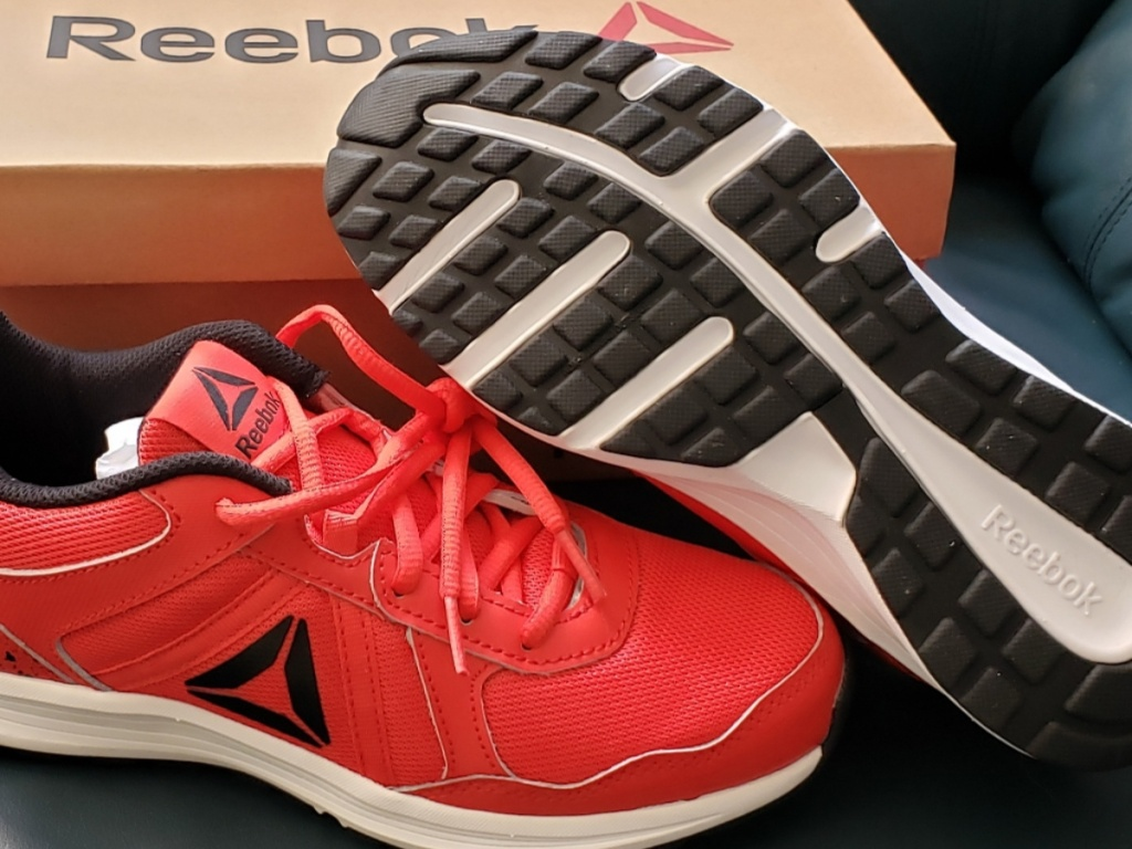 red and black kids shoes next to shoe box