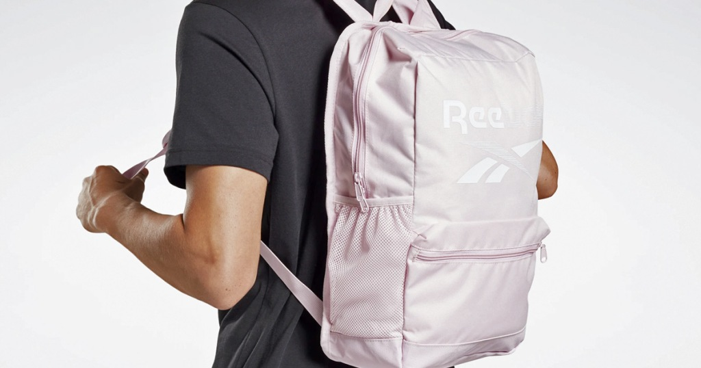 person in black shirt wearing a light pink reebok backpack