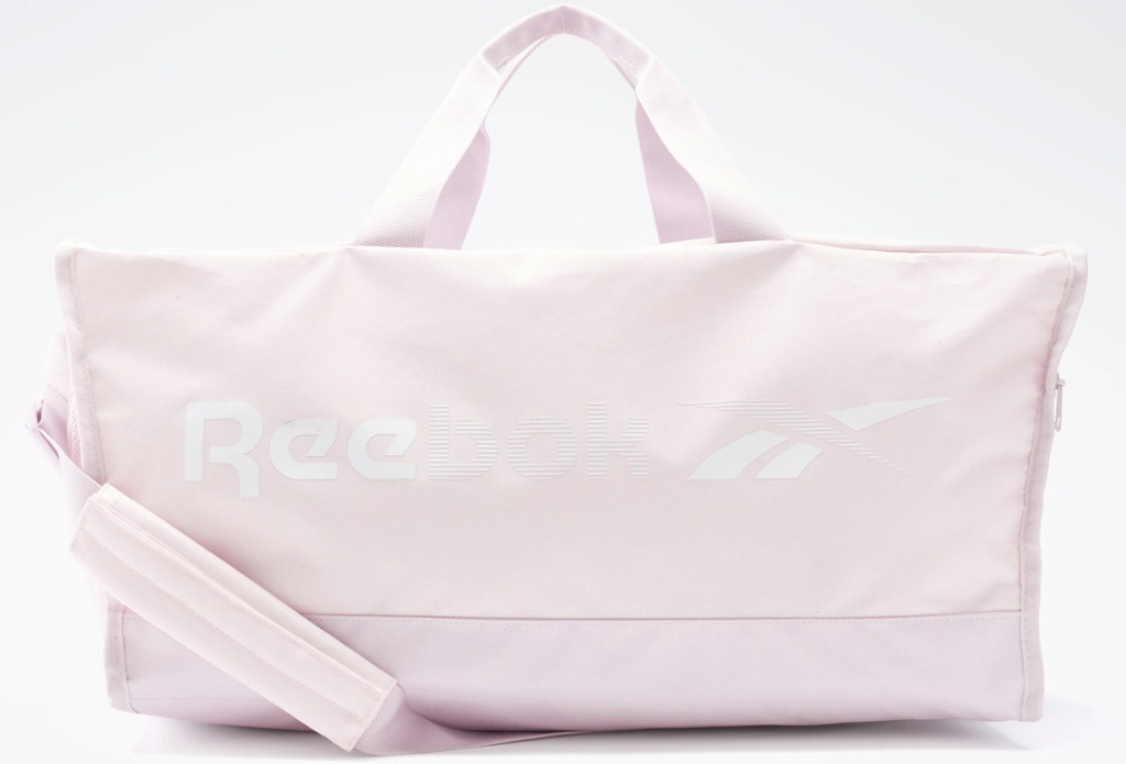 light pink duffel bag that says reebok on the side
