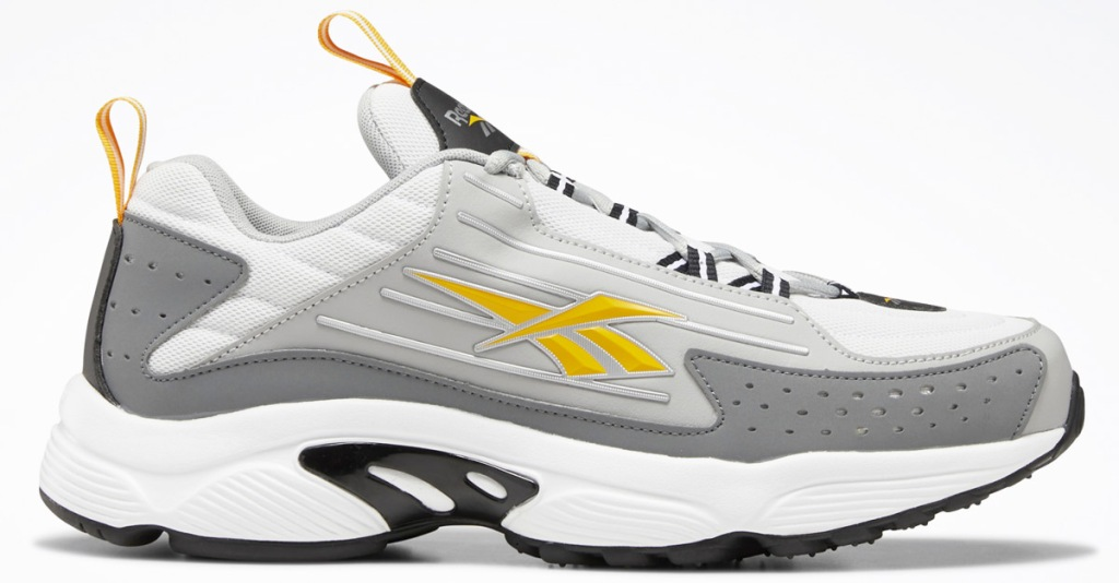 white and grey reebok shoe with yellow logo on side