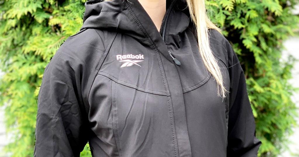 woman with blonde hair wearing black reebok jacket outside in front of greenery