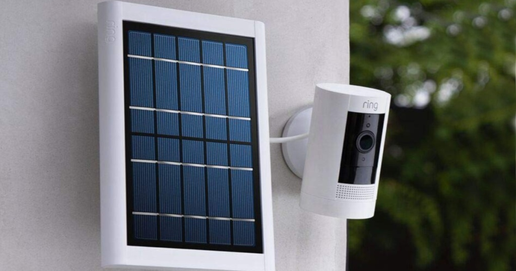 Ring security camera mounted on a wall next to a small solar panel