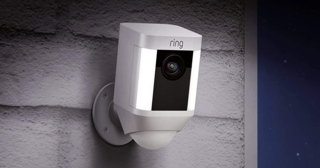 white smart security camera on side of home at night