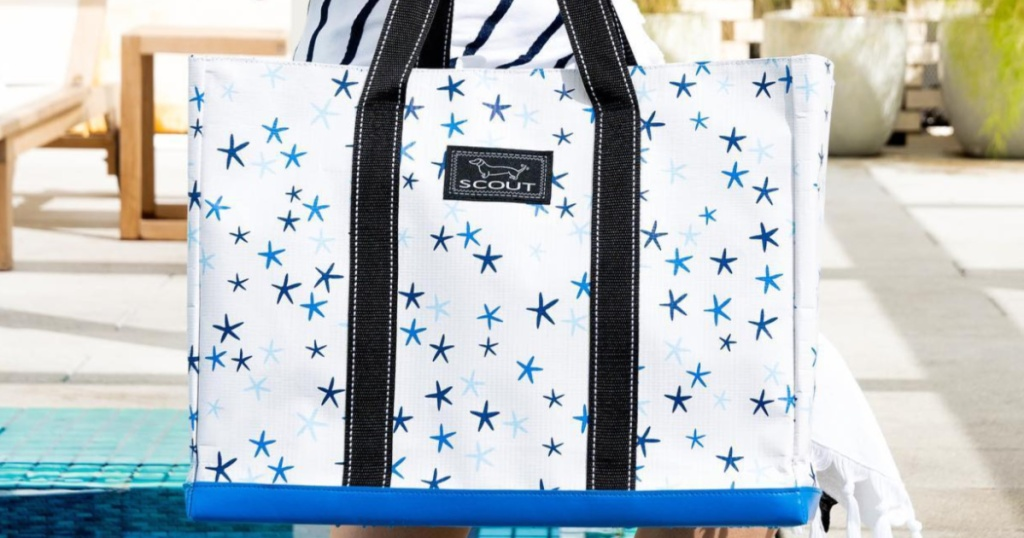 woman holding white and blue star patterned tote bag at pool