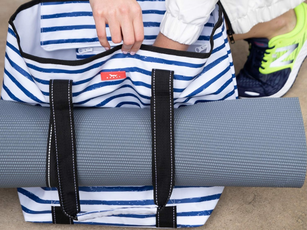 yoga mat in handles of blue and white striped tote bag