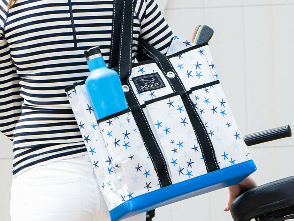 woman carrying white and blue star patterned tote bag over shoulder