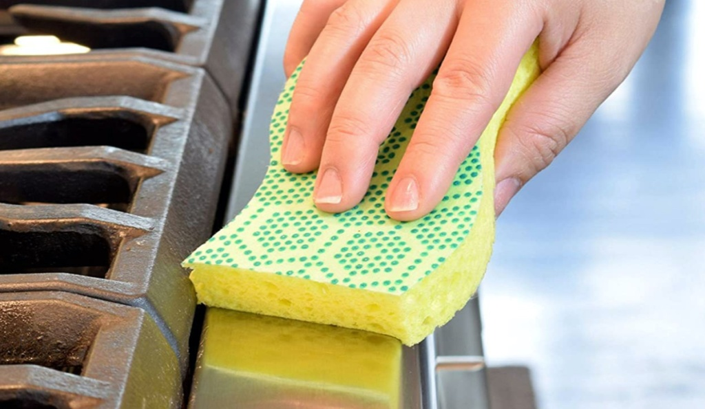 hand using yellow and green sponge on oven