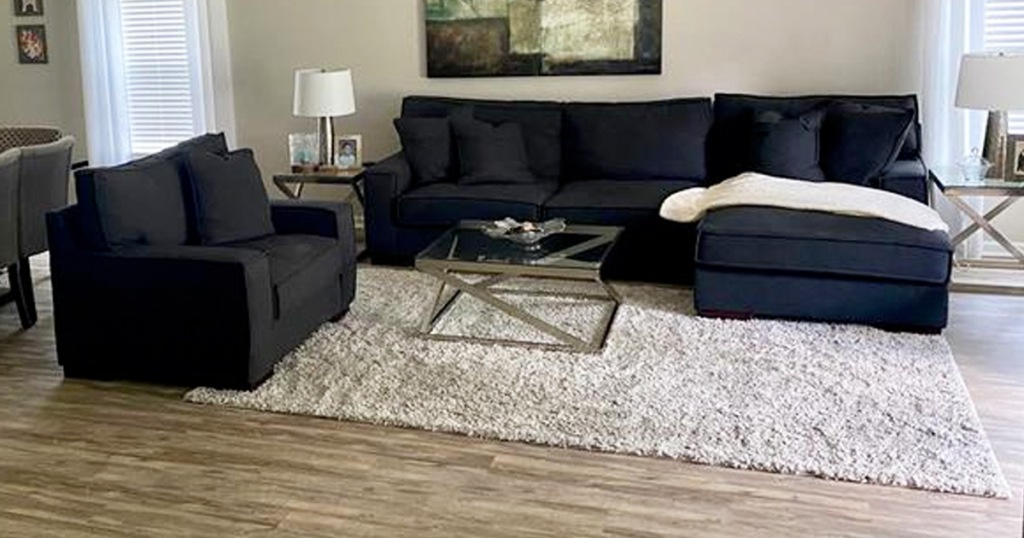 cream colored shag area rug in living room under black sectional sofa and love seat