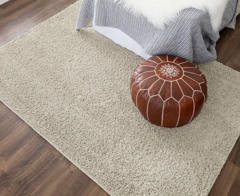 cream colored area rug on wood floor with brown round ottoman on it