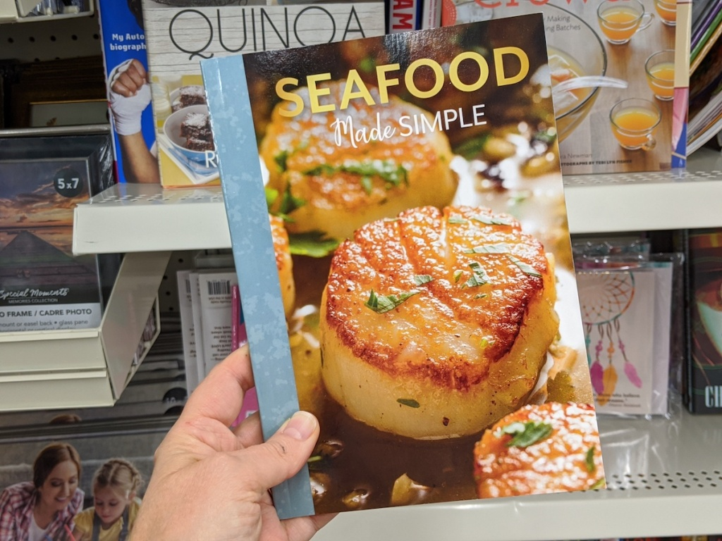 hand holding a Seafood cookbook