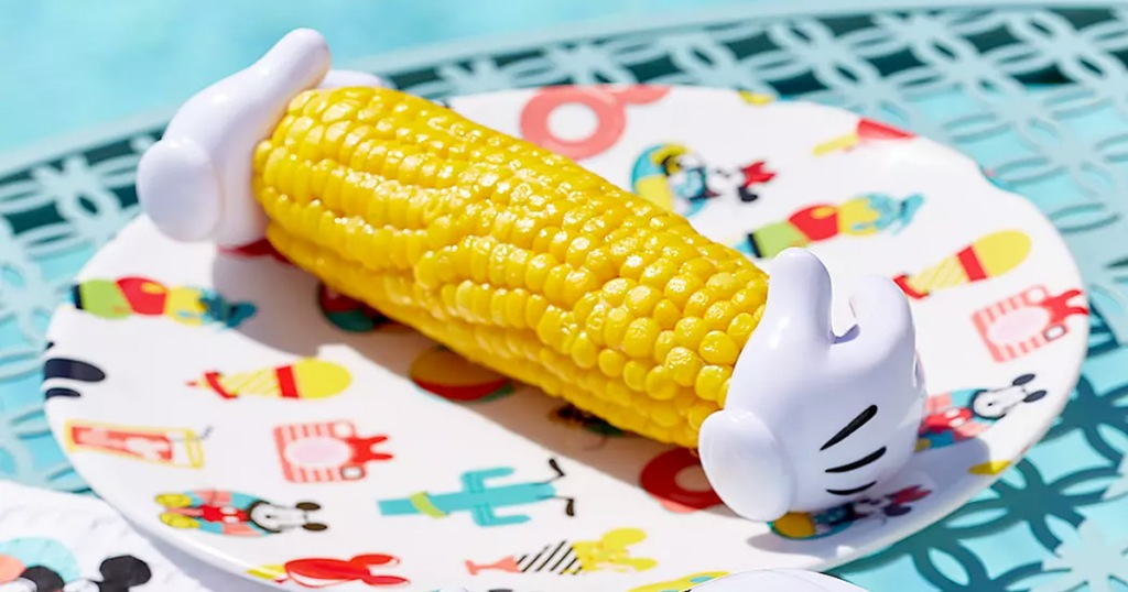 piece of corn sitting on disney themed plate with mickey glove corn holders stuck into sides of corn