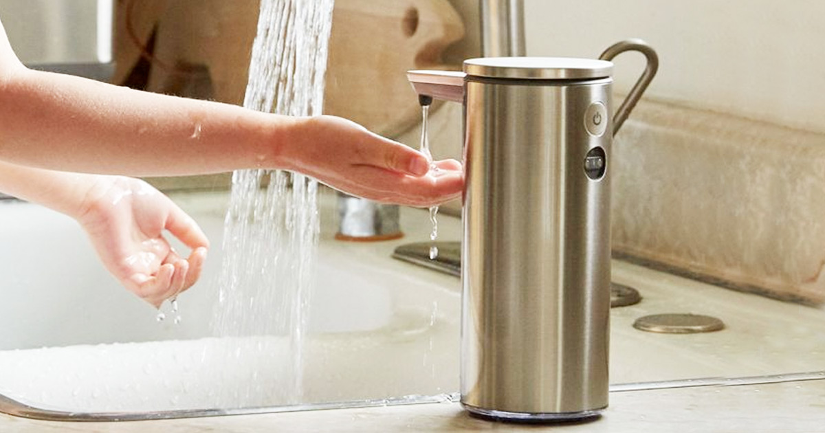 person putting hand under sensor soap dispenser with running water in background