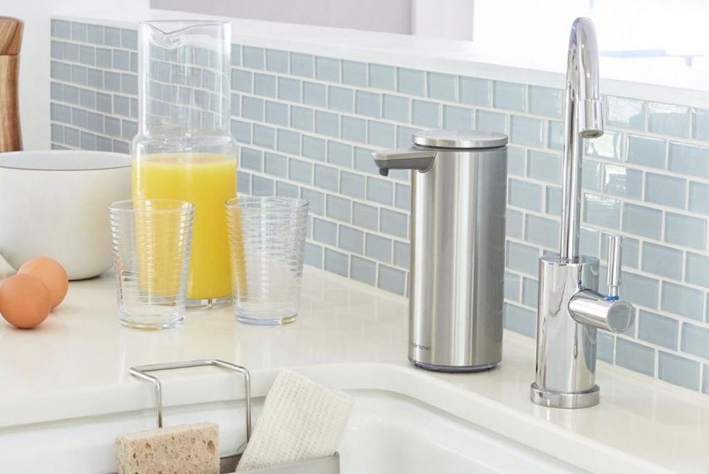 stainless steel colored soap dispenser next to chrome faucet and sink with light blue backsplash