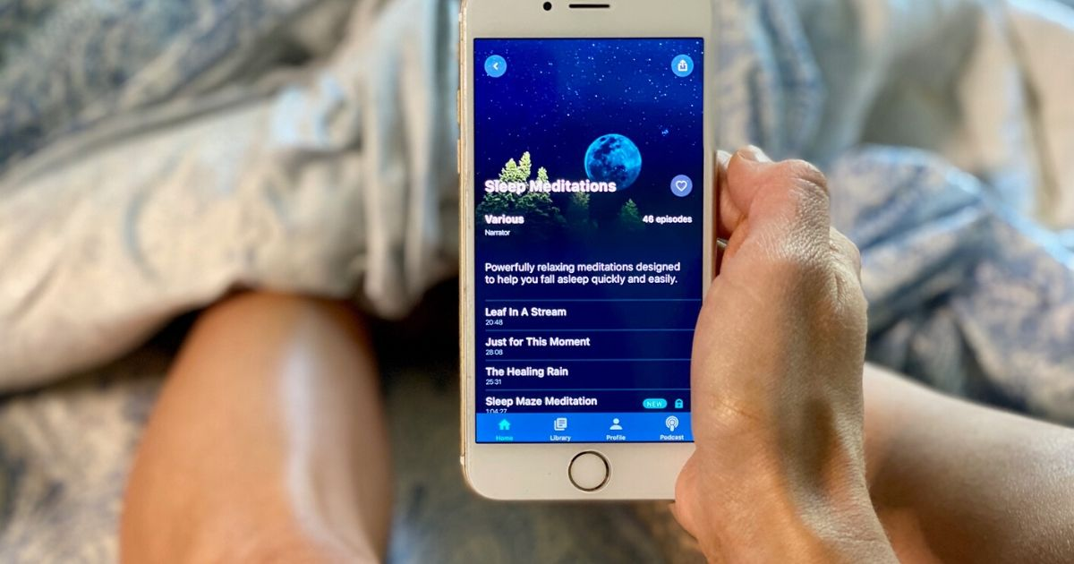 Person in bed with the Slumber sleep app open on a phone