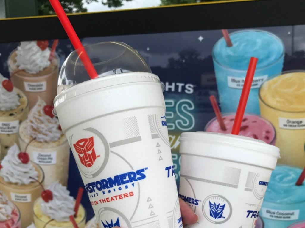 hand holding fast food milkshake and slushie in front of menu sign