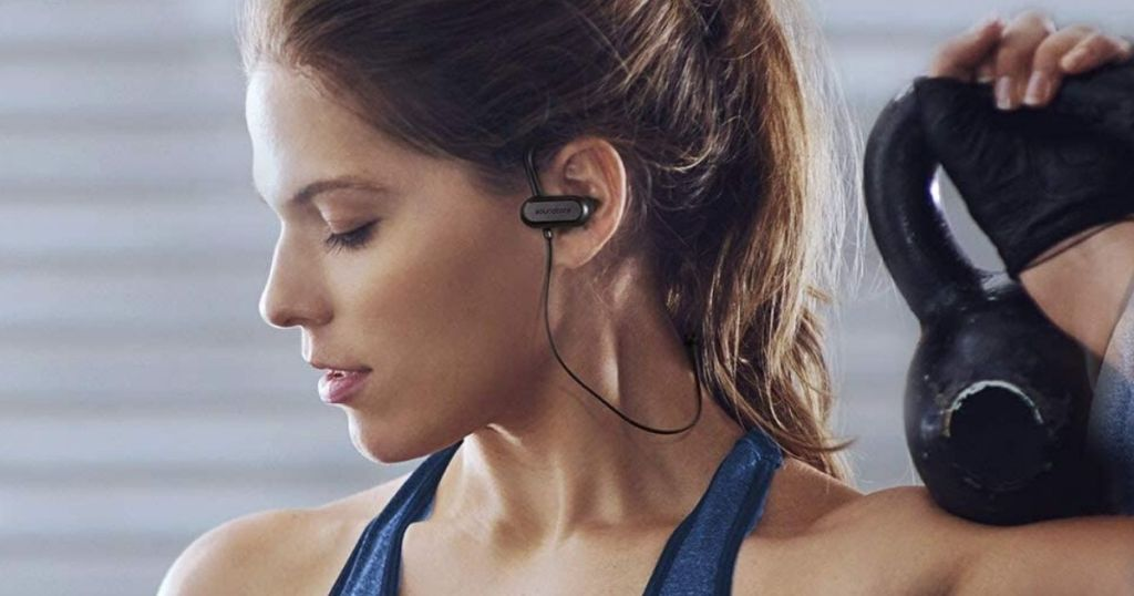 woman wearing in-ear headphones while working out