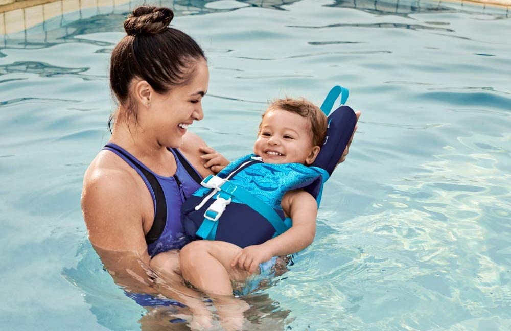 woman holding a child in a life jacket