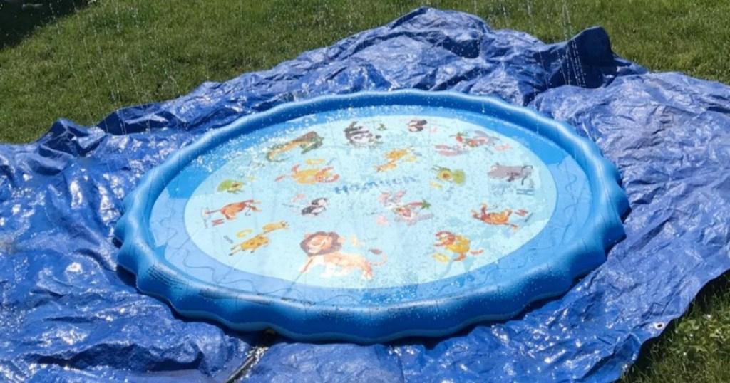 blue kids splash pad on top on blue tarp on lawn
