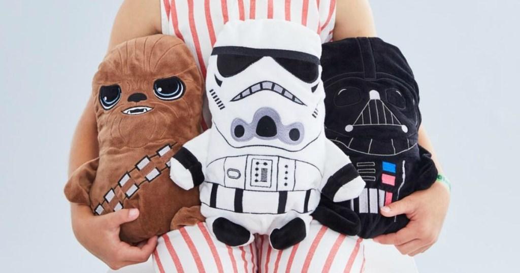 Child holding three Star Wars themed plush animals